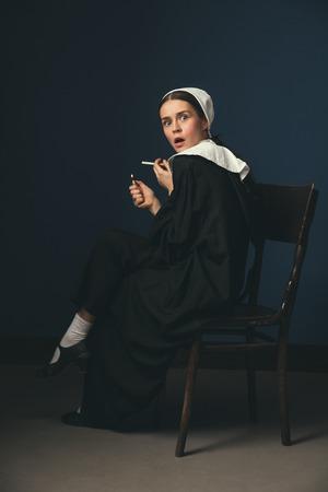 Finden Sie etwas Interessantes. Mittelalterliche junge Frau als Nonne in Vintage-Kleidung und weißem Mutch, die auf dem Stuhl auf dunkelblauem Hintergrund sitzt. Rauchen heimlich Zigarette. Konzept des Vergleichs von Epochen.