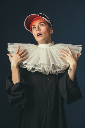 Impressed of brightness. Medieval young woman in black vintage clothing and red cap as a nun standing on dark blue background. Trying on modernity accessories. Concept of comparison of eras. Фото со стока