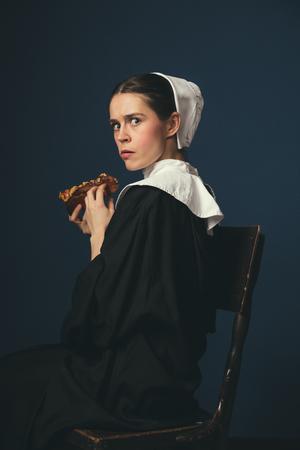 Cosa si nasconde nell'anima di una donna. Giovane donna medievale come suora in abiti vintage e mutch bianco seduto sulla sedia su sfondo blu scuro. Mangiare hot dog. Concetto di confronto di epoche.