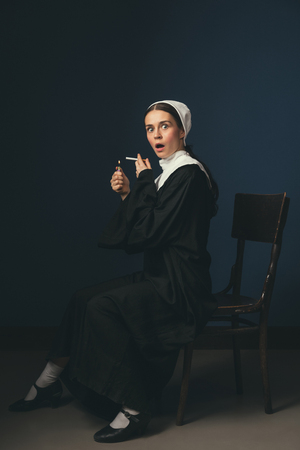 Will be confession. Medieval young woman as a nun in vintage clothing and white mutch sitting on the chair on dark blue background. Smoking cigarette in secret. Concept of comparison of eras.