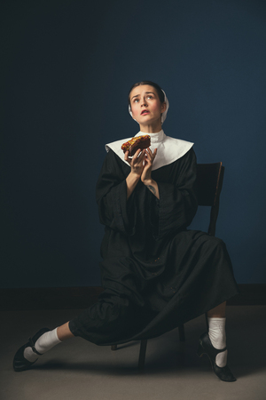With apology to the sky. Medieval young woman as a nun in vintage clothing and mutch sitting on the chair on dark blue background. Eating tasty hot dog or sandwich. Concept of comparison of eras.