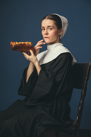 Secrets and sins - how it taste. Medieval young woman as a nun in vintage clothing and white mutch sitting on the chair on dark blue background. Eating hot dog. Concept of comparison of eras.