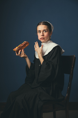 Unexpected confession, surprising moment. Medieval young woman as a nun in vintage clothing and white mutch sitting on the chair on dark blue background. Eating hot dog. Concept of comparison of eras.