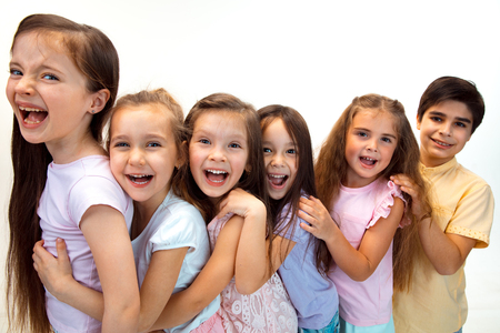 흰색 스튜디오 벽에 기대어 카메라를 바라보는 세련된 캐주얼 옷을 입은 행복한 귀여운 어린 소년 소녀들의 초상화. 키즈 패션과 인간의 감정 개념
