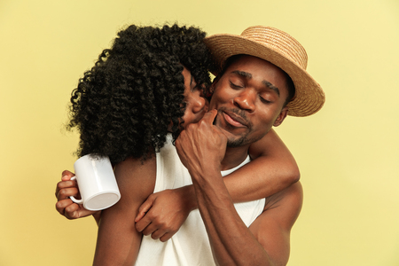 Wonderful moments together. Happy african american family posing on yellow studio background. Leisure, togetherness, relationship and human emotions concept.