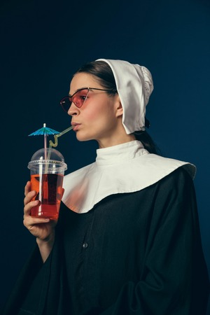 Long awaited lounge chilling. Medieval young woman as a nun in vintage clothing sitting on the chair on dark blue background. Drinking lemonad or coctail. Concept of comparison of eras. Banque d'images