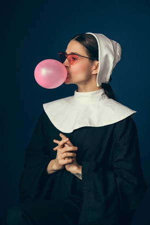 New emotions. Medieval young woman as a nun in vintage clothing and sitting on the chair with bright red glasses on dark blue background. Doing bubble up. Concept of comparison of eras. Banque d'images
