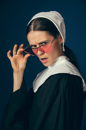 Youth forgives all. Medieval young woman as a nun in vintage clothing and white mutch sitting on the chair with bright red glasses on dark blue background. Concept of comparison of eras.