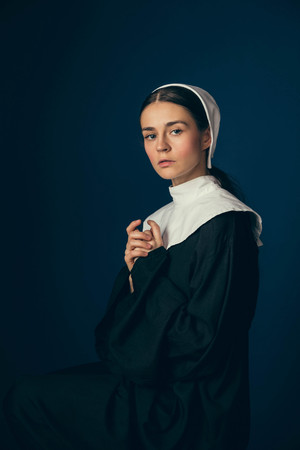 Hope and faith. Medieval young woman as a nun in vintage clothing and white mutch sitting on the chair on dark blue background. Concept of comparison of eras. Vintage portrait.