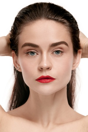 A beautiful female face. Perfect and clean skin of young caucasian woman on red studio background.