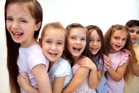 Het portret van gelukkige schattige kleine kinderen jongen en meisjes in stijlvolle casual kleding kijken camera tegen witte studio muur. Kindermode en menselijke emoties concept