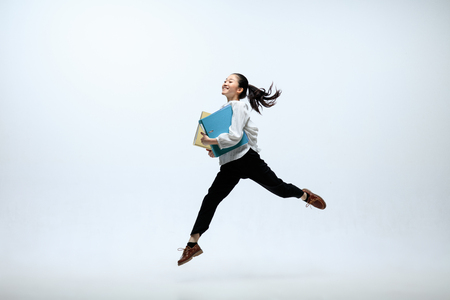 Getting faster and stronger. Happy woman working at office, jumping and dancing in casual clothes or suit isolated on white studio background. Business, start-up, working open-space concept.