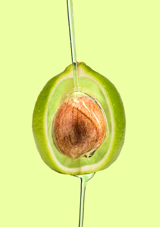 A paradox and hidden sense or deepest idea. Lime outside and avocado inside and pouring oil against green background. Modern design. Contemporary art collage. Concept of healthy food, creating, diet.