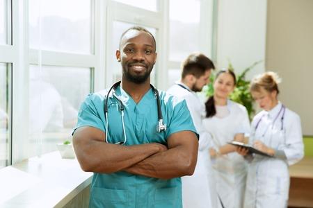 Gezondheidszorg mensen groep. Professionele Afro-Amerikaanse mannelijke arts die zich voordeed op ziekenhuiskantoor of kliniek. Medische technologie onderzoeksinstituut en arts personeel dienstverleningsconcept. Gelukkig lachende modellen. Stockfoto