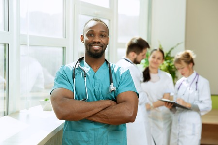 Healthcare people group. Professional african american male doctor posing at hospital office or clinic. Medical technology research institute and doctor staff service concept. Happy smiling models. Reklamní fotografie - 120532680