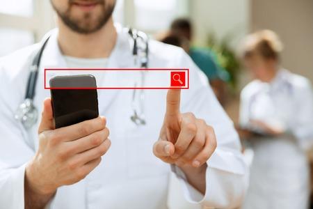 Médico varón caucásico profesional con teléfono en la oficina del hospital o clínica. Concepto de servicio de personal médico y tecnología médica. Dedo masculino tocando la barra de búsqueda vacía: se puede usar para insertar texto o imágenes.