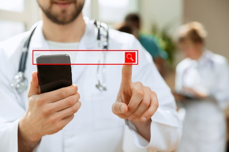 Professional caucasian male doctor with phone at hospital office or clinic. Medical technology and doctor staff service concept. Male finger touching empty search bar - can be used for insert text or pictures.