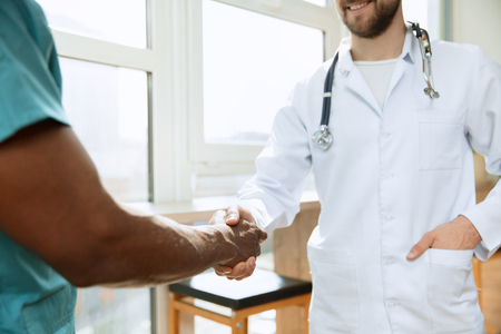 Deal. Concept of collaboration in medicine. Close up photo of two doctors shaking hands on gray hospital background. Advertising image about healthcare, health, clinic, medicine and teamwork.