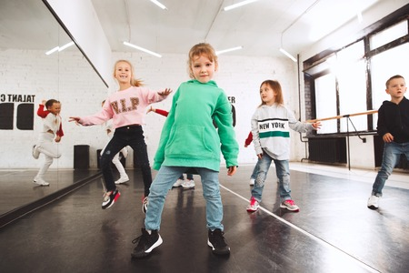 The kids at dance school. Ballet, hiphop, street, funky and modern dancers over studio background. Children showing aerobic element. Teens in hip hop style. Sport, fitness and lifestyle concept. Banque d'images - 120650577
