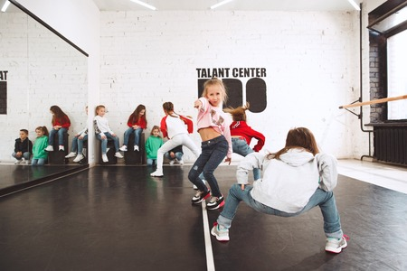 The kids at dance school. Ballet, hiphop, street, funky and modern dancers over studio background. Children showing aerobic element. Teens in hip hop style. Sport, fitness and lifestyle concept.