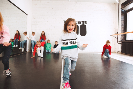 The kids at dance school. Ballet, hiphop, street, funky and modern dancers over studio background. Children showing aerobic element. Teens in hip hop style. Sport, fitness and lifestyle concept. 写真素材 - 120650816