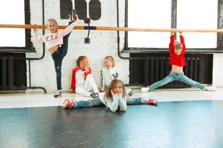 The kids sitting at dance school. Ballet, hiphop, street, funky and modern dancers concept. Studio background. Teens in hip hop style. Sport, fitness and lifestyle concept. Warm up and stretching. 写真素材 - 120650817