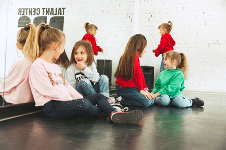 The kids sitting at dance school. Ballet, hiphop, street, funky and modern dancers concept. Studio background. Teens in hip hop style. Sport, fitness and lifestyle concept. Banque d'images - 120650843