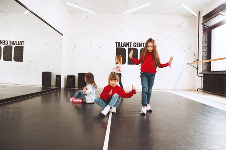 The kids at dance school. Ballet, hiphop, street, funky and modern dancers over studio background. Children showing aerobic element. Teens in hip hop style. Sport, fitness and lifestyle concept. 写真素材 - 120650880