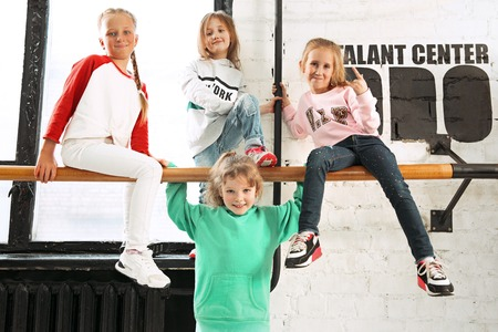 The kids sitting at dance school. Ballet, hiphop, street, funky and modern dancers concept. Studio background. Teens in hip hop style. Sport, fitness and lifestyle concept. Stock Photo