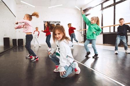 Los niños de la escuela de baile. Bailarines de ballet, hiphop, street, funky y modernos sobre fondo de estudio. Niños que muestran elemento aeróbico. Adolescentes en estilo hip hop. Concepto de deporte, fitness y estilo de vida. Foto de archivo