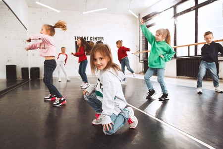 The kids at dance school. Ballet, hiphop, street, funky and modern dancers over studio background. Children showing aerobic element. Teens in hip hop style. Sport, fitness and lifestyle concept. Фото со стока - 120650961