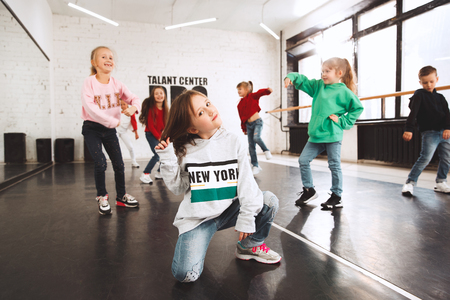 The kids at dance school. Ballet, hiphop, street, funky and modern dancers over studio background. Children showing aerobic element. Teens in hip hop style. Sport, fitness and lifestyle concept. 写真素材 - 120650962