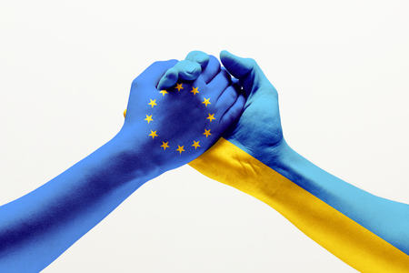 Unification of forces. Two male hands colored in flag of European Unity and Ukraine isolated on grey studio background. Concept of help, partnership of countries, political and economical relations.
