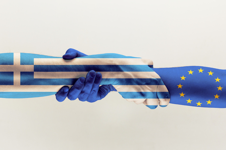 New way of relation. Male hands holding colored in EU and Greece flag isolated on gray studio background. Concept of help, commonwealth, partnership of countries, political and economical relations. Stock Photo