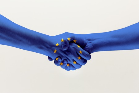 Cooperation agreement. Male hands shaking colored in blue EU flag isolated on gray studio background. Concept of help, commonwealth, unity of European countries, political and economical relations.