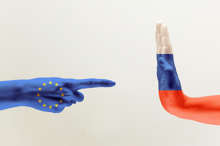 Confrontation, countries disagreement. Female and male hands colored in flags of European Unity and Russia isolated on grey background. Concept of political, economical or social aggressions. Stock Photo