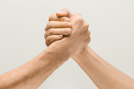 Friends greetings sign or disagreement. Two male hands competion in arm wrestling isolated on grey studio background. Concept of standoff, support, friendship, business, community, strained relations.