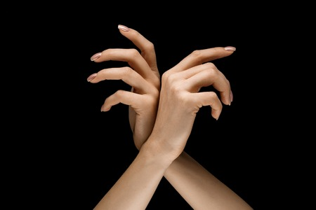 Choosing a right way. Male and female hands demonstrating a gesture of getting touch isolated on black studio background. Concept of human relations, relationship, feelings or business.