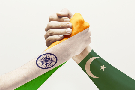 Intense communication. Two male hands competing in arm wrestling colored in Pakistan and India flags isolated on white studio background. Concept of economical and political relations, disagreement.