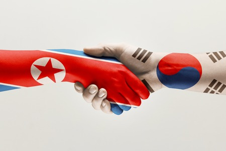 Lets try again. Two male hands shaking colored in flag of North and South Korea isolated on white studio background. Concept of help, partnership of countries, political and economical relations. Фото со стока