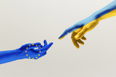 The creation of Adam. Two male hands colored in flag of European Unity and Ukraine isolated on grey studio background. Concept of help, partnership of countries, political and economical relations.
