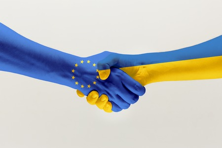 Welcome gesture. Two male hands shaking colored in flag of European Unity and Ukraine isolated on grey studio background. Concept of help, partnership of countries, political and economical relations.