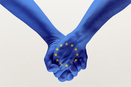 평화와 강함. 회색 스튜디오 배경에 격리된 파란색 EU 깃발을 들고 있는 남성 손. 도움의 개념, 연방, 유럽 국가의 통일, 정치 및 경제적 관계.