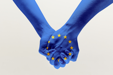 Peace for all the people. Male and female hands holding colored in blue EU flag isolated on gray studio background. Concept of help, unity of European countries, political and economical relations.