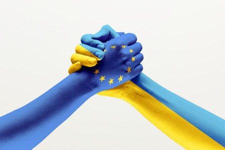 Brothers and friends. Two male hands holding colored in flag of European Unity and Ukraine isolated on grey studio background. Concept of help, partnership of countries, political and economical relations.