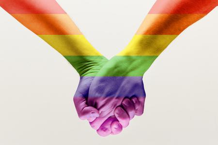 Recht, seinen eigenen Weg zu wählen. Loseup Schuss eines Paares Händchen haltend, gemustert wie die Regenbogenfahne isoliert auf weißem Studiohintergrund. Konzept von LGBT, Aktivismus, Gemeinschaft und Freiheit.