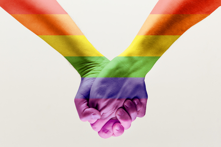 Right to choose your own way. loseup shot of a gay couple holding hands, patterned as the rainbow flag isolated on white studio background. Concept of LGBT, activism, community and freedom. Stock fotó - 120651044