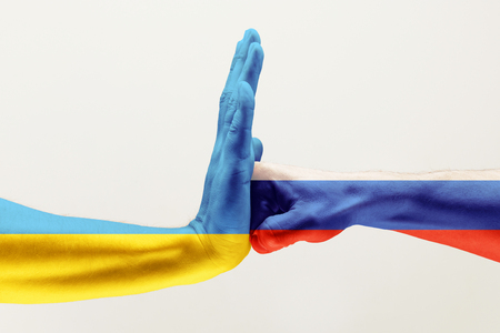 Stop the brothers hit. Two male hands fighting colored in Russian Federation and Ukraine flags isolated on white studio background. Concept of political, economical, social aggressions, disagreement. Stock Photo