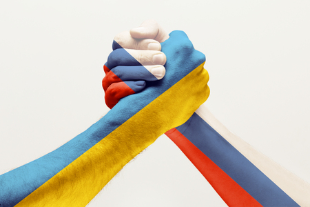 Stop to find out whos better. Two male hands fighting colored in Russia and Ukraine flags isolated on white studio background. Concept of political, economical, social aggressions, disagreement. Stock Photo