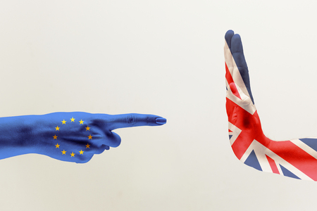 The accusations and anger. Male hands colored in United Kingdom and European Unity flags isolated on white studio background. Concept of brexit, political, economical, social, disagreement.